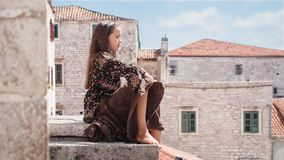 Chica joven linda que se sienta en el tejado de la ciudad vieja Niño femenino agradable en ciudad medieval Imágenes de archivo libres de regalías
