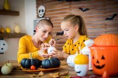 Chica joven linda que se sienta en una tabla, adornando las pequeñas calabazas blancas con su madre, un enfermo de cáncer DIY Hal imagen de archivo libre de regalías