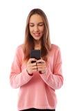 Chica joven linda que sostiene el teléfono móvil mientras que se opone a pizca Fotos de archivo libres de regalías