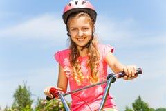 Chica joven linda que sostiene la bicicleta Foto de archivo libre de regalías