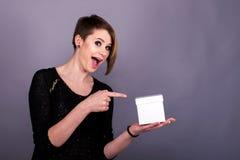 Chica joven linda que sostiene la caja en una mano y señalar Fotos de archivo libres de regalías