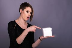 Chica joven linda que sostiene la caja en una mano y señalar imágenes de archivo libres de regalías