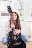 Chica joven linda que sostiene la guitarra Imagenes de archivo