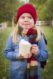Chica joven linda que sostiene la taza caliente del cacao con las melcochas Fotografía de archivo libre de regalías