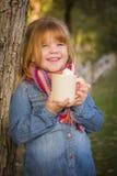 Chica joven linda que sostiene la taza del cacao con Marsh Mallows Outside Fotografía de archivo libre de regalías