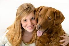 Chica joven linda que sostiene un perro Fotos de archivo libres de regalías