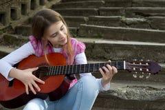 Chica joven linda que toca una guitarra contra escalera de piedra vieja Imagenes de archivo