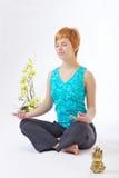 Chica joven meditating en un fondo ligero Imagenes de archivo