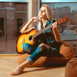 Chica joven moderna de la imagen cuadrada con una guitarra en manos Imágenes de archivo libres de regalías