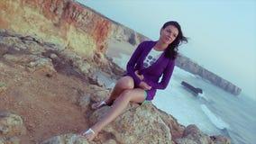 Chica joven morena en la chaqueta púrpura, pantalones cortos que se sientan en roca en el mar Tarde del verano holidays Sonrisa almacen de metraje de vídeo