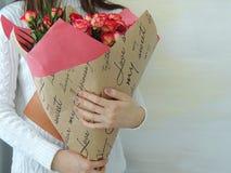 Chica joven, muchacha adolescente que sostiene el ramo de rosas rosadas, rojas Fotos de archivo