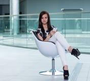 Chica joven muy atractiva que se sienta en una silla blanca con un elegante Fotos de archivo libres de regalías