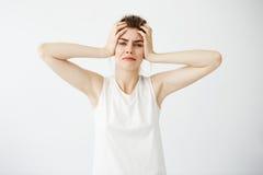 Chica joven nerviosa descontentada que lleva a cabo la cabeza que mira la cámara sobre el fondo blanco Foto de archivo libre de regalías
