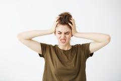 Chica joven nerviosa descontentada que lleva a cabo la cabeza que mira la cámara sobre el fondo blanco Dolor de cabeza Fotografía de archivo