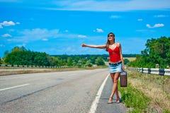 Chica joven o mujer hermosa en mini con la maleta que hace autostop a lo largo de un camino Fotografía de archivo libre de regalías