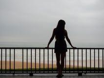 Chica joven o mujer hermosa que se coloca en un balcón o una terraza que pasa por alto el mar Fotografía de archivo
