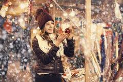 Chica joven ordinaria que elige los regalos de Navidad en el mercado Imagen de archivo libre de regalías