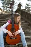 Chica joven pensativa con la guitarra que se sienta en las escaleras y que mira lejos Imagen de archivo