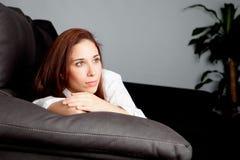 Chica joven pensativa en el sofá en casa Foto de archivo