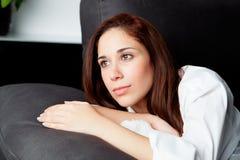 Chica joven pensativa en el sofá en casa Imagen de archivo libre de regalías