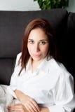 Chica joven pensativa en el sofá en casa Imagenes de archivo