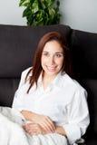 Chica joven pensativa en el sofá en casa Fotos de archivo
