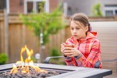 Chica joven pensativa que se sienta por el fuego imagen de archivo libre de regalías