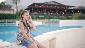 Chica joven por la piscina que habla en el teléfono metrajes