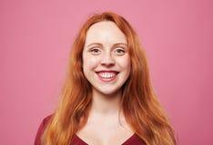 Chica joven positiva del pelirrojo que sonríe en la cámara Imágenes de archivo libres de regalías
