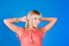 Chica joven positiva en un fondo azul Imagen de archivo libre de regalías