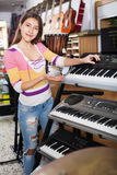 Chica joven positiva que elige el sintetizador Fotos de archivo libres de regalías