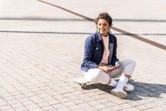 Chica joven positiva que se sienta en el monopatín Imagen de archivo libre de regalías