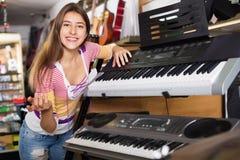 Chica joven positiva sonriente que elige el sintetizador Fotografía de archivo libre de regalías
