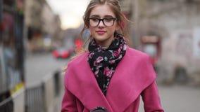Chica joven preciosa en una mirada elegante que camina abajo de la calle apretada de la ciudad, con una taza de café y pareciendo almacen de metraje de vídeo