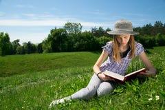 Chica joven preciosa que lee un libro mientras que se sienta en un campo hermoso de la hierba Fotografía de archivo