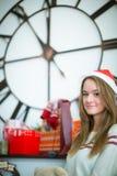 Chica joven preciosa que presenta con los regalos de la Navidad Imagenes de archivo