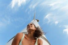 Chica joven progresiva en un fondo del cielo azul Adolescente fresco al lado de un molino de viento La juventud es un concepto fu Imagen de archivo libre de regalías