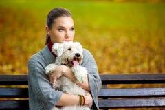 Chica joven que abraza su perro Imagen de archivo libre de regalías