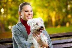 Chica joven que abraza su perro Fotos de archivo