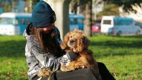 Chica joven que acaricia su perro almacen de metraje de vídeo