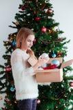 Chica joven que adorna el árbol de navidad Imagen de archivo libre de regalías
