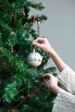 Chica joven que adorna el árbol de navidad con la bola Fotografía de archivo
