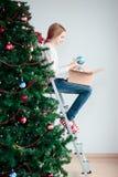 Chica joven que adorna el árbol de navidad con las bolas Foto de archivo libre de regalías