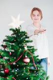 Chica joven que adorna el árbol de navidad con las luces Imágenes de archivo libres de regalías