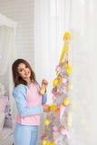 Chica joven que adorna el árbol del Año Nuevo Fotos de archivo