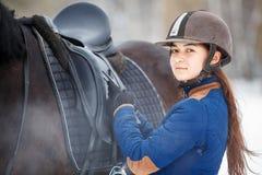 Chica joven que ajusta estribos antes de caballo de montar a caballo Imagenes de archivo
