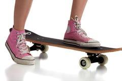 Chica joven que anda en monopatín con las zapatillas de deporte rosadas Imagen de archivo