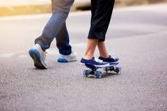 Chica joven que anda en monopatín con su papá que corre en el parque i al aire libre fotos de archivo