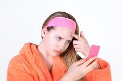 Chica joven que aplica la crema para el acné Mirada triste en el espejo imagen de archivo