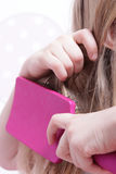 Chica joven que aplica su pelo con brocha Imagen de archivo libre de regalías